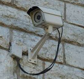 An outdoor surveillance camera attached to the outside of a building.