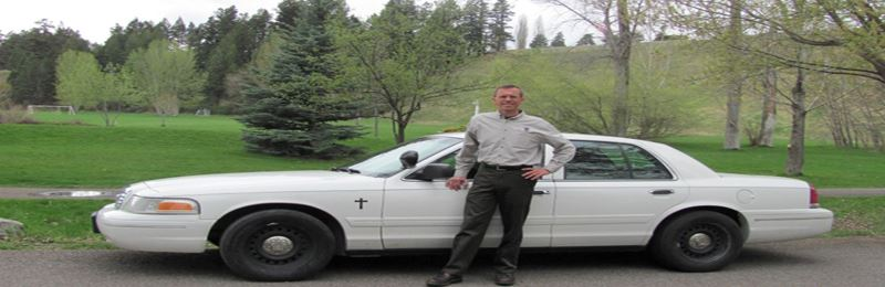 Image of Drew Buckner in front of white vehicle at a park