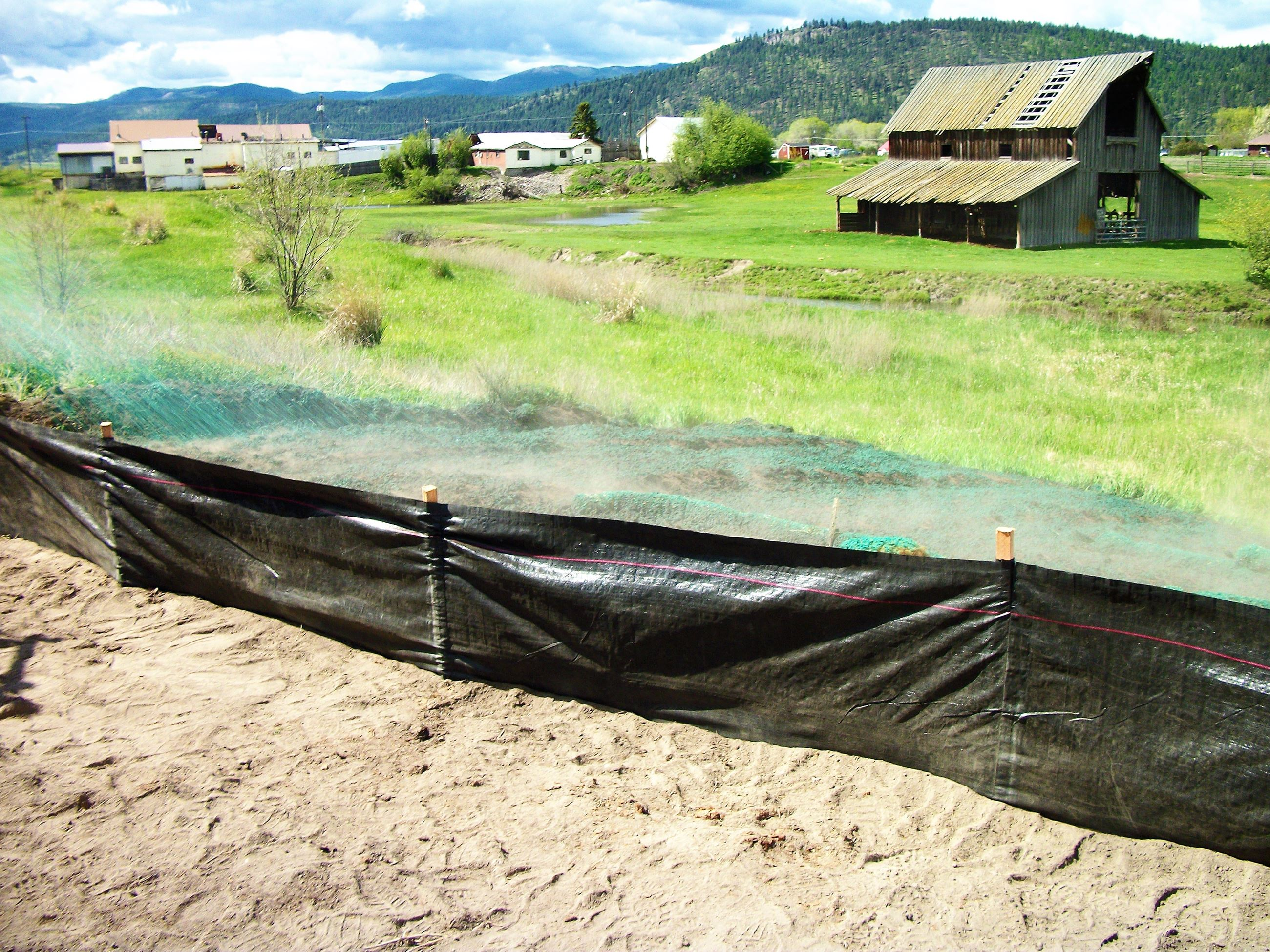 Silt fence protecting property and farm house in background